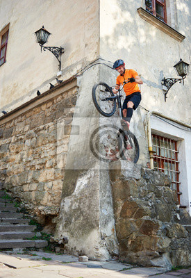 Plakat Young stuntman getting ready to jump with his mountain bike from the corner of ancient building, concept of extreme sport