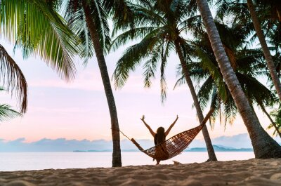 Plakat Young woman meeting morning sunrise sunlight sitting in a hammock and lazy stretching her body raising arms up on the sandy beach under the palm trees. Calm exotic places vacation concept image.