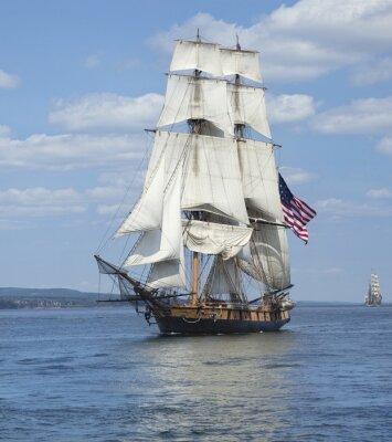 Plakat Żaglowiec z amerykańską flagą żeglowania po błękitnych wodach