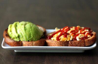 Zdrowe śniadanie. Chleb tostowy pełnoziarnisty, omlet (omlet) z sosem pomidorowym (ketchup) i świeże awokado na białym talerzu na ciemnym tle drewna