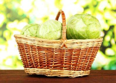Plakat Zielona kapusta w wiklinowym koszu, na jasnym tle