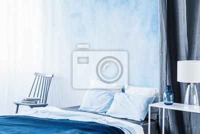 Tapeta Biała Lampa Na Stole Obok łóżka Z Granatową Pościelą W Sypialni